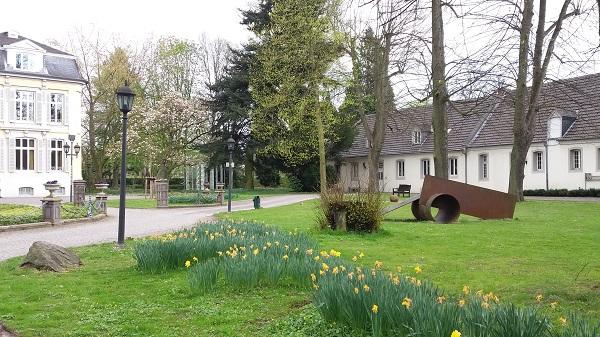 Bild des Rundwegs im Garten Schloss Morsbroichs mit Vorburg und Ausstellungsstücke